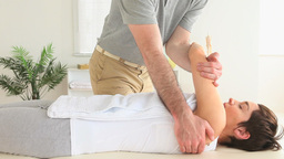 Chiropractor stretching the shoulder of a woman Footage