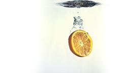 Orange slice splashing into water in super slow mo Stock Video Footage