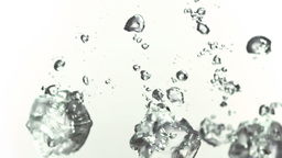 Ice cubes splashing into water in super slow motio Footage