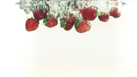 Strawberries splashing into water in super slow mo Stock Video Footage