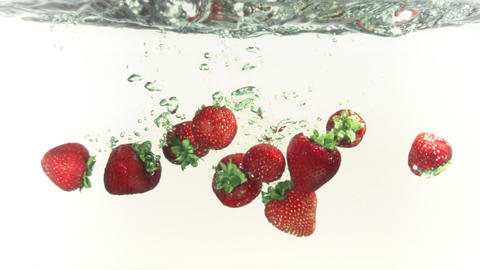 Strawberries splashing into water in super slow motion Stock Video Footage