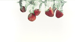 Strawberries falling into water in super slow moti Footage