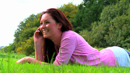 Lying woman with mobile phone on lawn Stock Video Footage