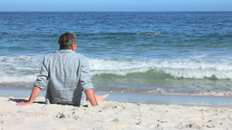 Man sitting at beach Stock Video Footage