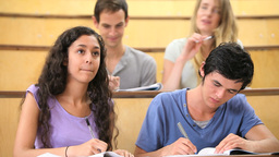 Students taking notes while their classmates are c Footage
