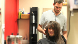 Hairdresser drying a students hair Stock Video Footage
