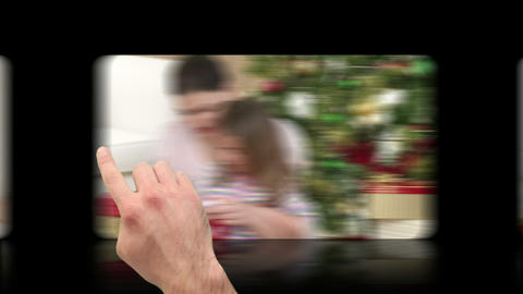 Hand pressing and scrolling through christmas videos Animation