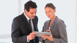 Business man and woman looking at a tablet Footage