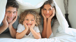 A family under the bed sheets smiling Footage