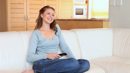 Woman sitting on the couch changing the channels Footage