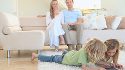 Couple looking their children playing on the floor Footage