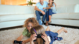 Children playing video games to the on a carpet Footage