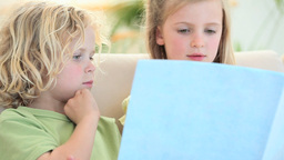 Children looking a book Stock Video Footage