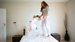 Mother and daughter jumping on a bed Footage
