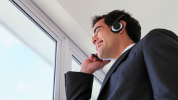 Man looking outside while calling with a headset Footage