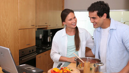 Laughing couple looking a recipe on a laptop Footage
