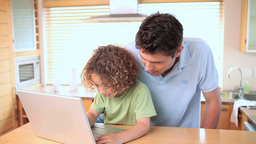 Boy looking at a laptop screen with his father Stock Video Footage
