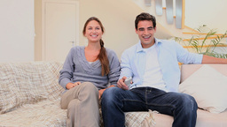 Laughing couple watching television Footage