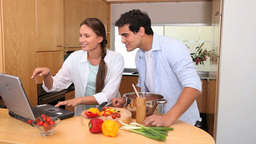 Couple using a laptop are cooking together Stock Video Footage