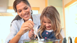 Little girl mixing salad with her mother Footage