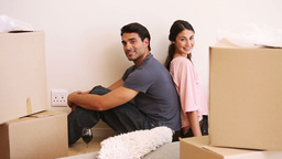 Couple sitting back to back in a room with boxes Footage