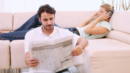 Man reading a newspaper and his girlfriend listens to music Live Action