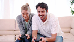 Young woman wining a game against her boyfriend Stock Video Footage