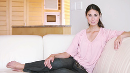 Young woman sitting on a couch Footage