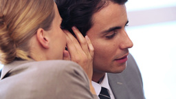Businesswoman telling a secret to her colleague Stock Video Footage