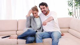 Smiling couple sitting on the couch while watching Footage