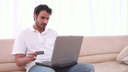 Man using his laptop and a credit card Footage