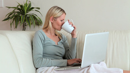 Woman drinking from a cup as she types on a laptop Stock Video Footage