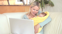 Woman holding a child is making a video call Footage