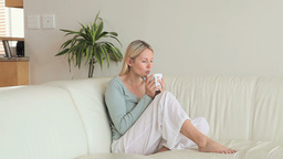 Woman sitting on a sofa drinking coffee Stock Video Footage