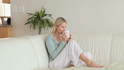Woman sitting on a sofa drinking coffee Footage