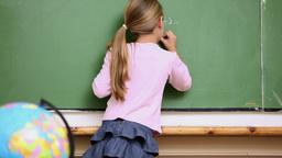 Blonde Girl Writing On The Blackboard stock footage