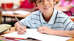 Smiling boy writing on his notebook Footage