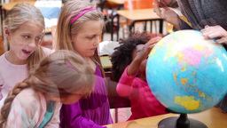 Happy pupils looking at a globe Footage