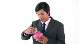 Businessman putting notes in a piggy bank Stock Video Footage