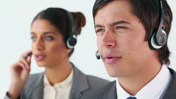 Smiling call centre agents using headsets Stock Video Footage
