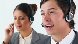 Smiling call centre agents using headsets Footage