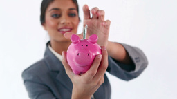 Smiling brunette putting notes in a piggy bank Stock Video Footage