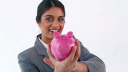 Smiling brunette putting notes in a piggy bank Footage