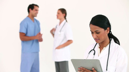 Doctor standing in front of her colleaugues Stock Video Footage