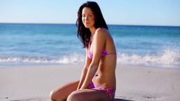 Brunette woman sitting on the sand Footage