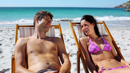 Happy couple lying on deck chairs Stock Video Footage