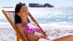 Brunette Woman Relaxing On A Deck Chair stock footage