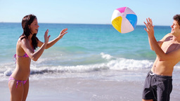 Smiling couple playing with a beach ball Footage