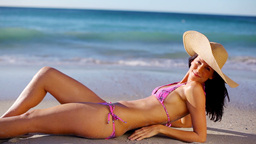 Smiling brunette lying on the sand Stock Video Footage
