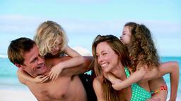Happy parents giving their children a piggyback Footage